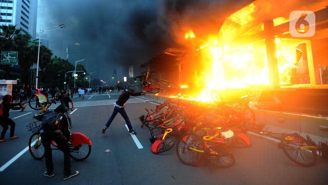 Massa membakar sepeda di halte Transjakarta, Jalan MH. Thamrin, Jakarta, Kamis (8/10/2020). Aksi anarkis massa dilakukan setelah bentrok dengan petugas kepolisian di kawasan Patung Kuda, Jakarta.(merdeka.com/Arie Basuki)