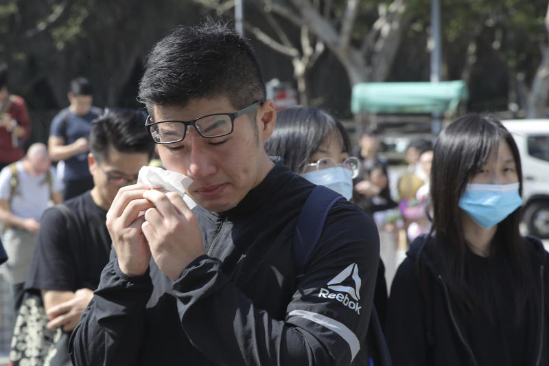 A man cries as he attends a makeshift memorial for Chow Tsz-Lok after a graduation ceremony was disrupted at the University of Science and Technology in Hong Kong on Friday, Nov. 8, 2019. Chow, a student from the University who fell off a parking garage after police fired tear gas during clashes with anti-government protesters died Friday, in a rare fatality after five months of unrest that intensified anger in the semi-autonomous Chinese territory. (AP Photo/Kin Cheung)