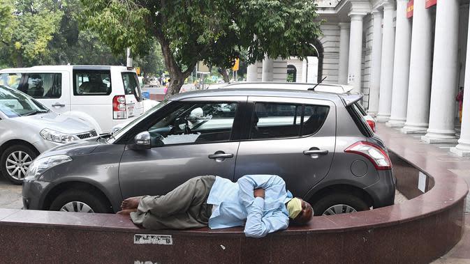 Seorang pria tidur siang di pusat perbelanjaan di New Delhi (16/9/2020). Total kasus Covid-19 di India melampaui lima juta pada 16 September, data kementerian kesehatan menunjukkan Pandemi meluas cengkeramannya di negara tersebut. (AFP/Sajjad Hussan)