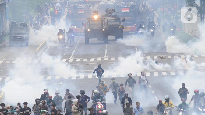 Petugas Brimob Polri menembakkan gas air mata untuk membubarkan massa usai terjadi lemparan batu di Jalan MH Thamrin, Jakarta, Selas (13/10/2020). Massa pengunjuk rasa yang menolak Omnibus Law akhirnya dibubarkan aparat. (merdeka.com/Arie Basuki)