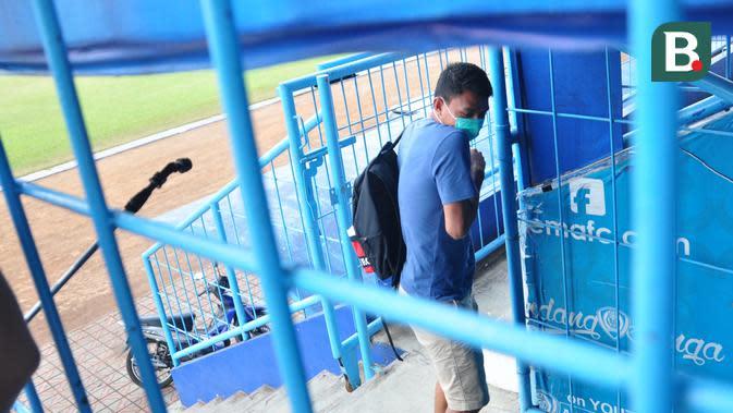 Striker Arema FC, Dedik Setiawan, tampak terkejut dan refleks menghindari semprotan disinfektan sebelum sesi latihan perdana Singo Edan di Stadion Kanjuruhan, Senin (3/8/2020) sore WIB. (Bola.com/Iwan Setiawan)