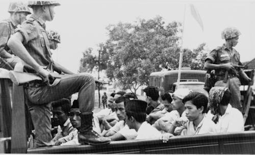"FILE - In this Oct. 30, 1965 file photo, members of the Youth Wing of the Indonesian Communist Party (Pemuda Rakjat) are guarded by soldiers as they are taken by an open truck to prison in Jakarta after they were rounded up by the army following a crackdown on communists after an abortive coup d'etat against President Sukarno's government earlier in the month. A new American-directed documentary, ""The Act of Killing,"" challenges widely held views about hundreds of thousands of deaths carried out across Indonesia from 1965 to 1966 in the name of fighting communism. It explores the country's darkest open secret by allowing former mass killers to re-enact their horrors on screen. (AP Photo/File)"