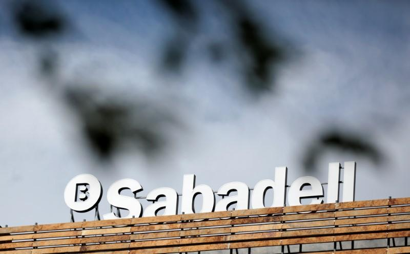 The Banco Sabadell logo can be seen behind leaves on top of a building outside Madrid, Spain