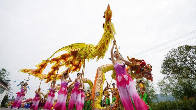 Warga desa mengenakan kostum tradisional ambil bagian dalam pertunjukan rakyat di Distrik Tongliang, China (19/9/2020). Pertunjukan tari naga dan kegiatan rakyat lainnya digelar untuk merayakan festival panen petani China yang jatuh pada Equinox Musim Gugur setiap tahunnya. (Xinhua/Liu Chan)