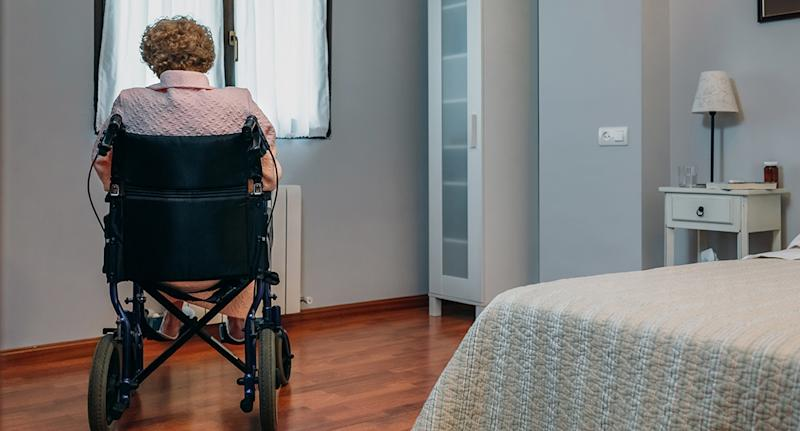An elderly woman sits in a wheelchair in the corner of a room.