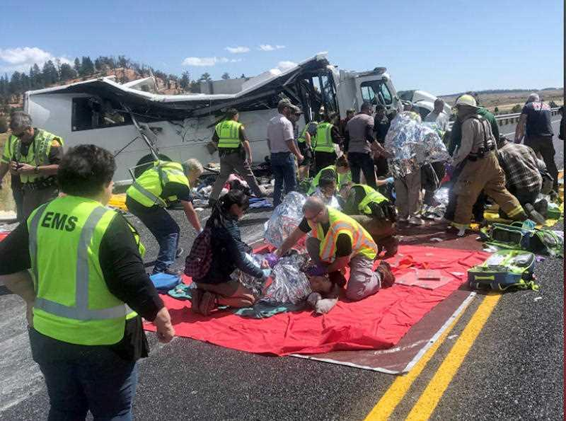 In this photo released by the Garfield County Sheriff's Office, Emergency Medical Services personnel assist victims of a bus crash near Bryce Canyon National Park in southern Utah.