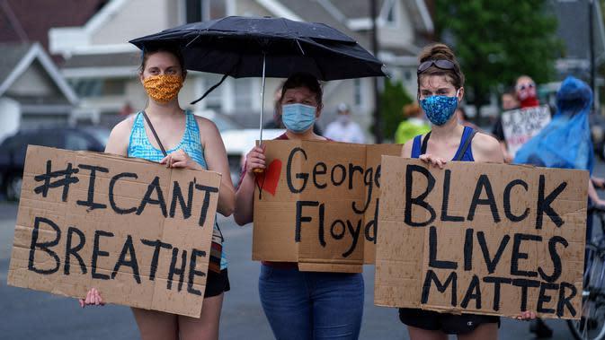 Sejumlah wanita memegang spanduk saat unjuk rasa atas kematian George Floyd oleh polisi di dekat TKP di Minneapolis, Minnesota, Amerika Serikat, Rabu (27/5/2020). Mayoritas demonstran hadir sambil membawa spanduk bertuliskan