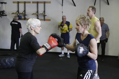 In this photo taken March 19, 2013, Michelle Stoneburner, left, spars with instructor Christine Timberlake during a workout at Rock Steady Boxing in Indianapolis. Timberlake has been with Rock Steady Boxing since 2006. Her husband,Tom, was diagnosed with Parkinson's disease in 2000. (AP Photo/Michael Conroy)