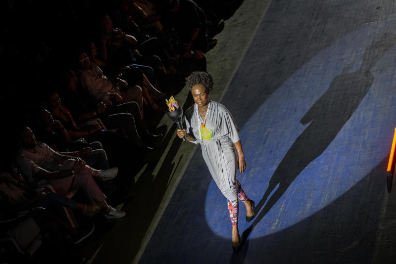 """Former 800-meter star and two time world champion, Cuban Ana Fidelia Quirot, wears a creation from """"Clandestina,"""" the first Cuban independent urban fashion brand, during a launches for the 2020 collection called Sports Glories in Havana, Cuba, Friday, Nov. 22, 2019. (AP Photo/Ramon Espinosa)"""