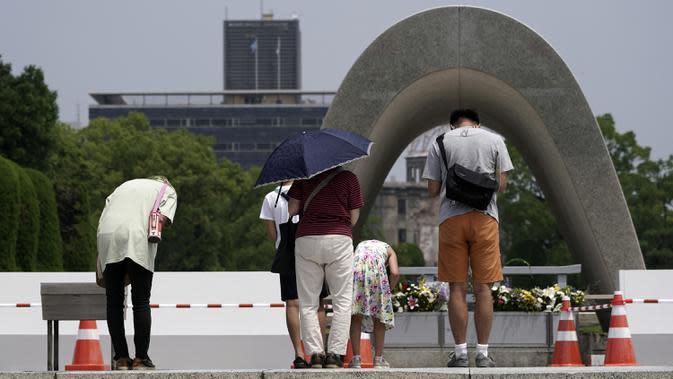 Warga menaruh hormat di depan cenotaph untuk para korban bom atom di Hiroshima, Jepang, Senin (3/8/2020). Jepang akan memperingati 75 tahun bom atom di Hiroshima pada 6 Agustus 2020. (AP Photo/Eugene Hoshiko)FOTO: Jepang Bersiap Memperingati 75 Tahun Bom Hiroshima