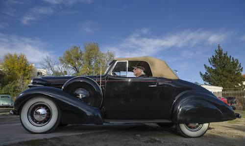 "In this photo taken Monday, Jan. 7, 2013, car collector, Garvin Kotzin, 63, who owns several cars featured in the ""Gangster Squad"" film, poses with his 1936 Oldsmobile convertible in Los Angeles. To bring the story of mobster Mickey Cohen's reign over post-war Los Angeles to life, the director of ""Gangster Squad"" employed Sean Penn, Josh Brolin, Ryan Gosling and more than 100 irreplaceable vintage American cars. (AP Photo/Damian Dovarganes)"