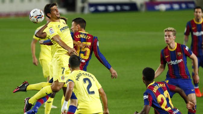 Pemain Barcelona, Clement Lenglet, berebut bola dengan pemain Villareal, Gerard Moreno, pada laga Liga Spanyol di Stadion Camp Nou, Senin (28/9/2020). Barcelona menang dengan skor 4-0. (AP Photo/Joan Monfort)