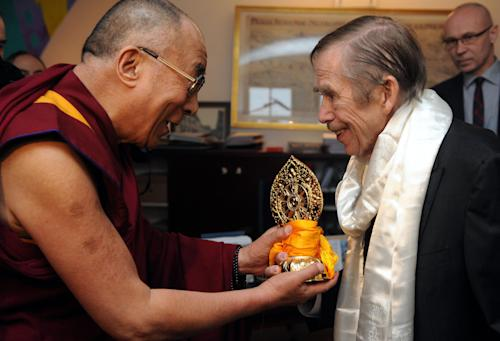 FILE - in this Dec. 10 2011 file photo Tibetan spiritual leader the Dalai Lama, left, hands a present to Czech ex-president Vaclav Havel, right, during their meeting in Prague, Saturday, Dec. 10, 2011. Havel, the dissident playwright who wove theater into politics to peacefully bring down communism in Czechoslovakia and become a hero of the epic struggle that ended the Cold War, died Sunday Dec. 18, 2011 in Prague. He was 75. (AP Photo,CTK/Katerina Sulova) SLOVAKIA OUT