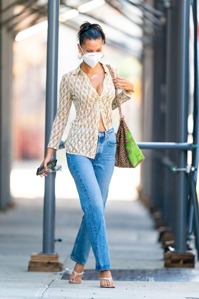 """<p>Hadid walks the streets of New York in a blue jeans, a printed button-down, gold hoops earrings, heeled sandals by <a href=""""https://www.fwrd.com/product-alexander-wang-ivy-85-logo-thong-sandal-in-sandstone/AWAN-WZ303/"""" target=""""_blank"""">Alexander Wang</a>, a leopard-print bag by Chrome Hearts, and, of course, a face mask. </p>"""