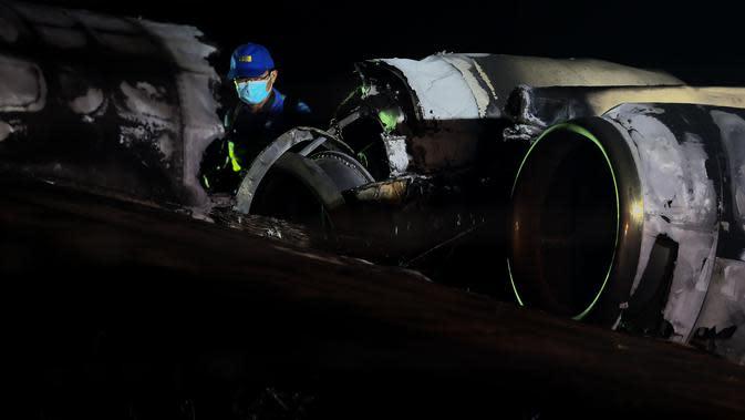 Petugas memeriksa puing-puing pesawat yang mengalami kecelakaan di ujung landasan pacu 24 di Bandara Internasional Ninoy Aquino, Manila, Filipina (29/3/2020). Kecelakaan terjadi di area runway. Pesawat yang bertujuan ke Jepang itu dilaporkan terbakar ketika baru lepas landas. (Xinhua/Rouelle Umali)