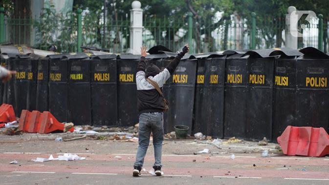 Pengunjuk rasa terlibat bentrok dengan polisi di Jalan Medan Merdeka Timur, Jakarta, Kamis (8/10/2020). Bentrokan terjadi akibat massa yang memaksa masuk ke depan Istana Negara untuk berunjuk rasa terkait penolakan UU Cipta Kerja. (Liputan6.com/Immanuel Antonius)