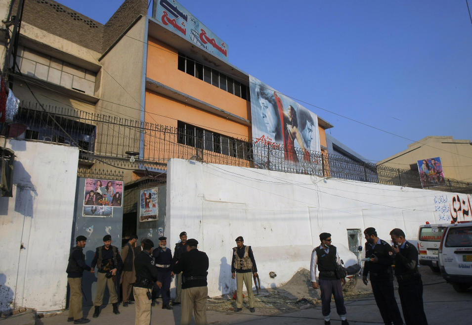 "Pakistani police officers gather outside a movie theater following a grenade attack that killed and wounded many people in Peshawar, Pakistan, Tuesday, Feb. 11, 2014. About 80 people were watching a movie called ""Yarana,"" which means friendship in Pashto, said an official. No one immediately claimed responsibility for the attacks, which come days after Pakistan began a peace process with Taliban militants fighting in the country's northwest to end the violence that has killed more than 40,000 people in recent years. (AP Photo/Mohammad Sajjad)"