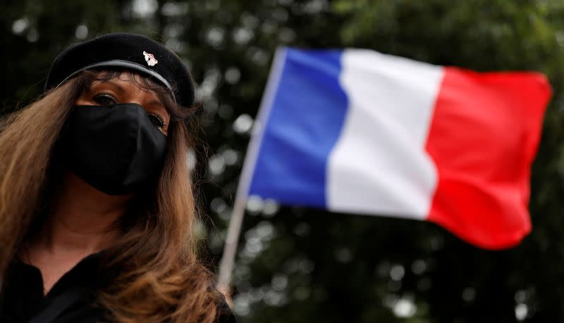 A supporter of police forces wears a protective face mask as she demonstrates in front of the French police headquarters in Paris