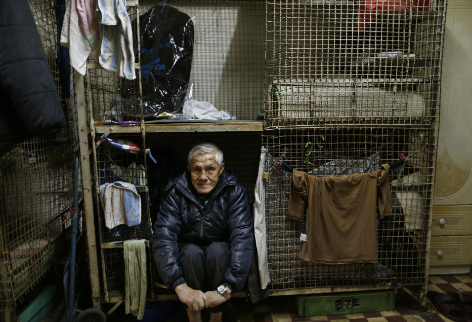 In this Jan. 25, 2013 photo, 77-year-old Yeung Ying Biu sits partially inside the cage, measuring 1.5 square meters (16 square feet),  which he calls home, in Hong Kong.  For many of the richest people in Hong Kong, one of Asia's wealthiest cities, home is a mansion with an expansive view from the heights of Victoria Peak. For some of the poorest, home is a metal cage. Some 100,000 people in the former British colony live in what's known as inadequate housing, according to the Society for Community Organization, a social welfare group. (AP Photo/Vincent Yu)