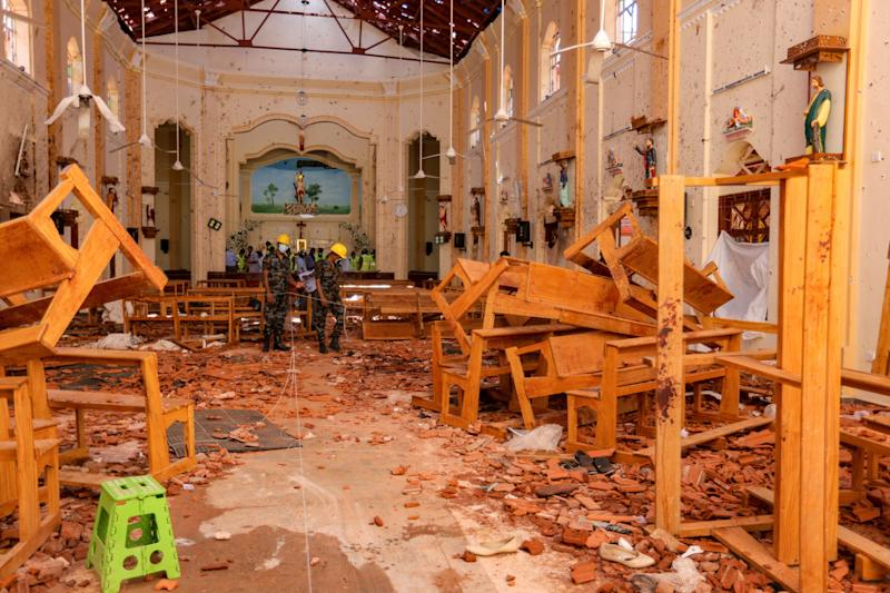 Sri Lankan soldiers inspect the damage inside St Sebastian's Church. Source: Getty Images