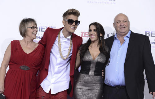 """Singer Justin Bieber, second from left, poses with grandmother Diane Dale, left, his mother Pattie Mallette, second from right, and his grandfather Bruce Dale at the premiere of the feature film """"Justin Bieber's Believe"""" at Regal Cinemas L.A. Live on Wednesday, Dec. 18, 2013, in Los Angeles. (Photo by Dan Steinberg/Invision/AP)"""