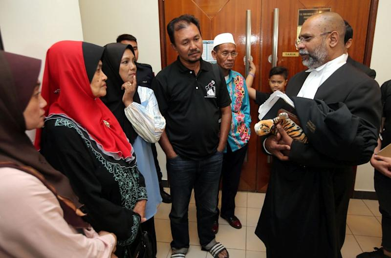 Kamarulnizam Ismail's family speak to their lawyer M. Visvanathan at the Ipoh High Court August 8, 2019. — Picture by Farhan Najib