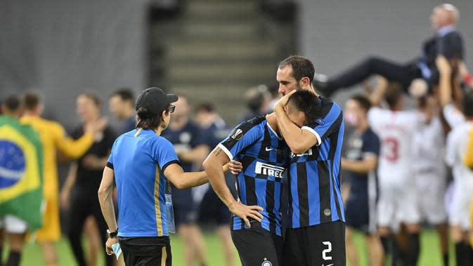Pemain Inter Milan, Diego Godin, menenangkan Lautaro Martinez usai gagal meraih gelar juara Liga Europa 2019/2020 di Stadion RheinEenergie, Sabtu (22/8/2020) dini hari WIB. Inter Milan kalah 2-3 atas Sevilla. (AFP/Martin Meissner/pool)