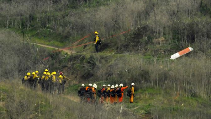 Sejumlah petugas berusaha mengevakuasi korban jatuhnya helikopter di Calabasas, California, Minggu (26/1/2020). Legenda NBA, Kobe Bryant, menjadi salah satu korban tewas pada kecelekaan helikopter berjenis Sikorsky S-76B itu. (AP/Mark J. Terrill)