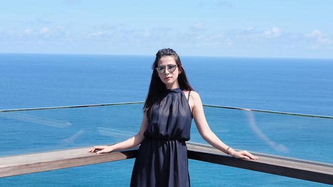 Pemilik 691 ribu followers di Instagram selalu berhasil memadupadankan baju yang ia kenakan dengan background saat berfoto. Seperti baju warna hitam sangat cocok dengan background lautan warna biru. Gayanya yang modis ini sangat menarik untuk diikuti. (Liputan6.com/IG/@rinadiana_8)