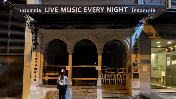 Seorang wanita berdiri di depan restoran yang tutup di kawasan hiburan malam Lan Kwai Fong, Hong Kong (5/5/2020). (AFP/May James)