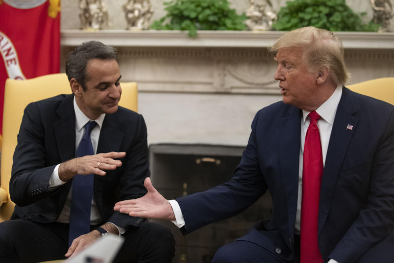 President Donald Trump, right, reaches to shake hands with Greek Prime Minister Kyriakos Mitsotakis during a meeting in the Oval Office of the White House, Tuesday, Jan. 7, 2020, in Washington. (AP Photo/Alex Brandon)