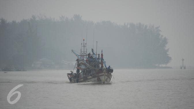 Nelayan berlayar dengan perahu di sungai Narathiwat yang diselimuti kabut asap, Thailand, Senin (5/10/2015). Kabut asap dari kebakaran hutan di Indonesia kini menyelimuti provinsi di wilayah selatan Thailand. (AFP PHOTO/Madaree TOHLALA)