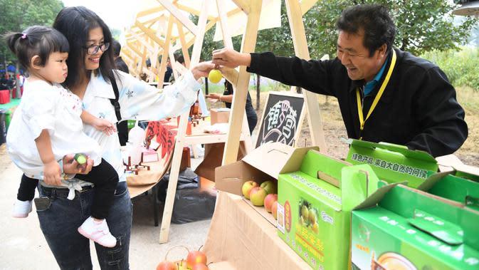 Warga melihat produk-produk pertanian yang dipamerkan pada pembukaan acara perayaan untuk menandai festival panen petani China di Distrik Pinggu, Beijing, ibu kota China, pada 24 September 2020. (Xinhua/Ren Chao)