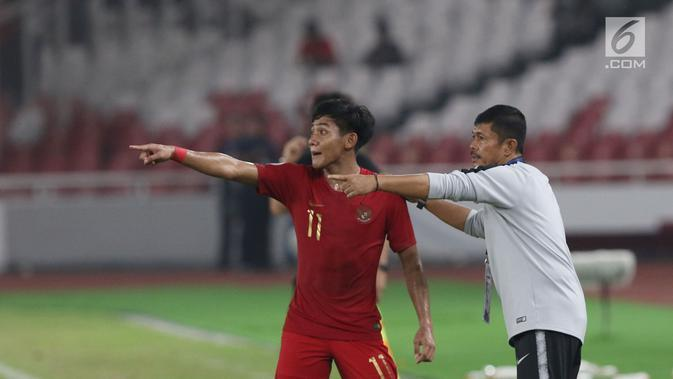 Bek timnas Indonesia -19, Firza Andika (kiri) menerima arahan pelatih Indra Sjafri saat melawan Uni Emirat Arab U-19 pada penyisihan Grup A Piala AFC U-19 2018 di Stadion GBK, Jakarta, Rabu (24/10). Indonesia unggul 1-0. (Liputan6.com/Helmi Fithriansyah)