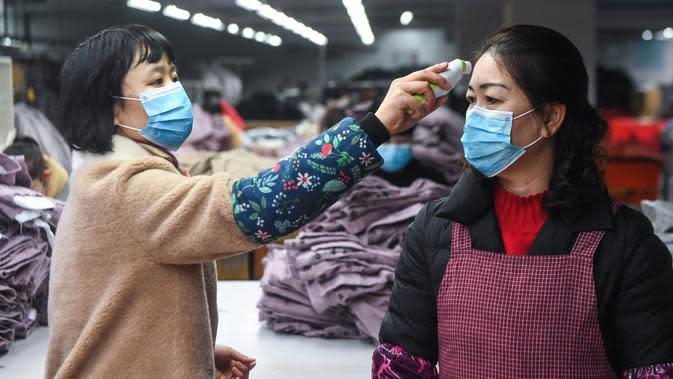 Karyawan diukur suhu badannya di Hangzhou Jiefeng Garments Co. Ltd., Hangzhou, Provinsi Zhejiang, China, Rabu (12/2/2020). Di bawah arahan dan dukungan otoritas setempat, banyak perusahaan di Zhejiang kembali beroperasi setelah melakukan pencegahan dan pengendalian wabah virus corona. (Xinhua/Xu Yu)