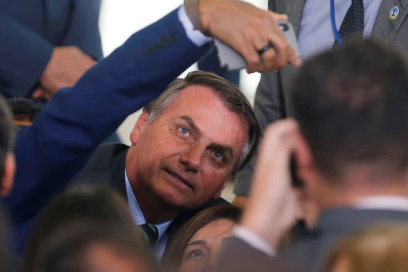 FILE PHOTO: Brazil's President Jair Bolsonaro poses for pictures after an inauguration ceremony of the new Culture Secretary Regina Duarte (not pictured) at the Planalto Palace, in Brasilia