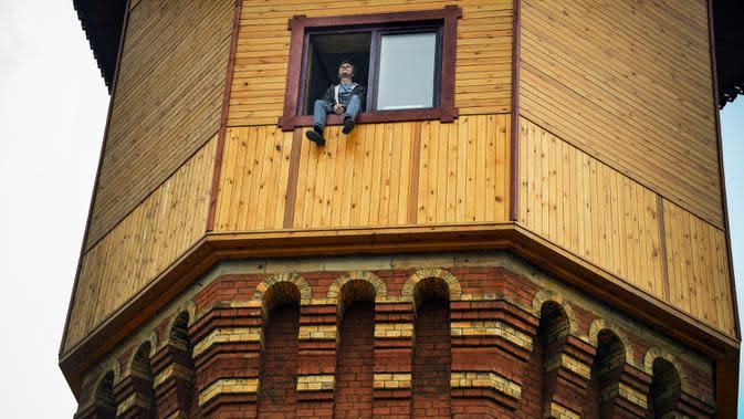 Pengusaha Rusia Alexander Lunev duduk di jendela bekas menara air, yang diubah menjadi apartemen, di kota Tomsk, Siberia pada 7 September 2020. Alexander Lunev mulai membangun kembali menara air yang dibuat pada 1895 tersebut, menjadi sebuah apartemen untuk dirinya. (Alexander NEMENOV / AFP)