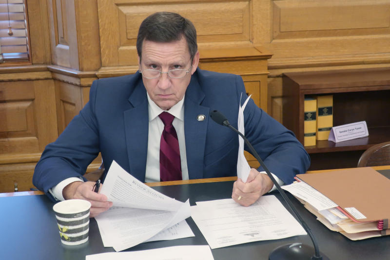State Sen. Dennis Pyle, R-Hiawatha, pauses to answer a reporter's questions while reading documents ahead of a Senate committee meeting on the governor's power during a pandemic, Tuesday, May 19, 2020, at the Statehouse in Topeka, Kan. Pyle and other Republicans want to curb the governor's power, believing that Democratic Gov. Laura Kelly has gone too far to check the spread of the novel coronavirus. (AP Photo/John Hanna)