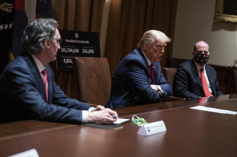 President Donald Trump speaks during a meeting with North Dakota Gov. Doug Burgum, left, and Colorado Gov. Jared Polis, in the Cabinet Room of the White House, Wednesday, May 13, 2020, in Washington. (AP Photo/Evan Vucci)