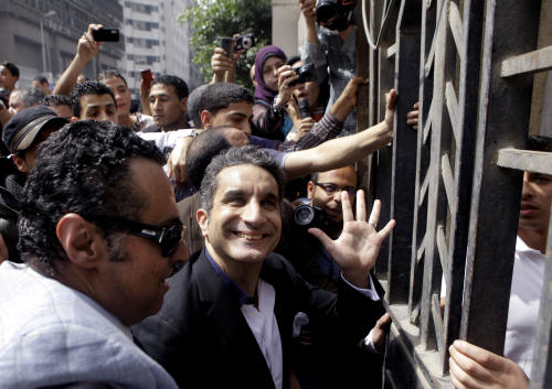 "FILE - In this Sunday, March 31, 2013 file photo, Egyptian popular television satirist Bassem Youssef, who has come to be known as Egypt's Jon Stewart, waves to is supporters as he enters Egypt's state prosecutors office to face accusations of insulting Islam and the country's Islamist leader in Cairo, Egypt. After more than four months away, the man known as ""Egypt's Jon Stewart"" returns the airwaves Friday in a country radically different from the one he previously mocked. Satirist Bassem Youssef's weekly ""El-Bernameg,"" or ""The Program"" in Arabic, mocked the country's first elected Islamist president and his supporters for mixing religion and politics, took them to task for failing to be inclusive or deliver on people's demands for change_ to the extent that some said he was one of the main reasons people turned against Mohammed Morsi. (AP Photo/Amr Nabil, File)"