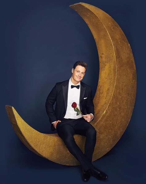 A photo of The Bachelor Australia Matt Agnew wearing a tuxedo, holding a red rose and sitting on a crescent moon.
