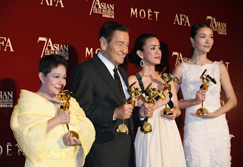 From left, Philippines actress Nora Aunor, Philippines actor Eddie Garcia, Japanese actress Makiko Watanabe and Chinese actress Qi Xi pose with their trophies after winning the Best Actress Award, Best Actor Award, Best Supporting Actress Award and Best Newcomer Award at the Asian Film Awards as part of the 37th Hong Kong International Film Festival in Hong Kong Monday, March. 18, 2013. (AP Photo/Kin Cheung)