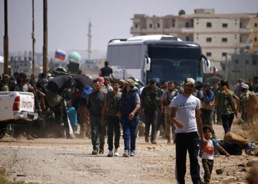 Hundreds of fighters and some relatives, carrying suitcases packed with clothes, boarded around 15 buses in Daraa city
