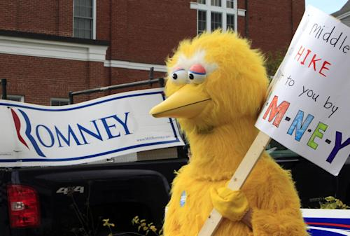 A person dressed as Big Bird holds a sign outside Republican presidential candidate, former Massachusetts Gov. Mitt Romney's headquarters, Monday, Oct. 8, 2012 in Derry, N.H. where House Speaker John Boehner of Ohio was about to speak to supporters. (AP Photo/Jim Cole)