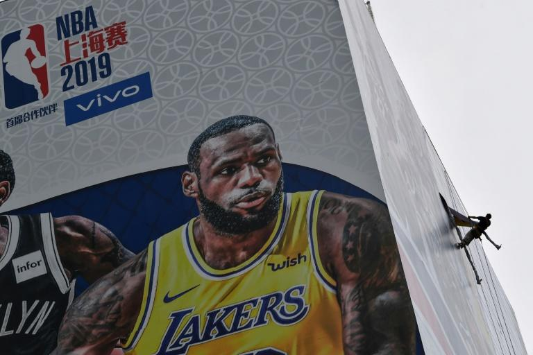 A worker on the side of a building in Shanghai removes a promotional banner for a National Basketball Association preseason game in China, after an NBA executive's comments on Hong Kong roiled ties between China and the league
