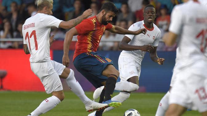 Striker Spanyol, Diego Costa, berusaha melewati gelandang Swiss, Valon Berhami, pada laga persahabatan di Stadion La Ceramica, Vila-real, Minggu (3/6/2018). Kedua negara bermain imbang 1-1. (AFP/Jose Jordan)