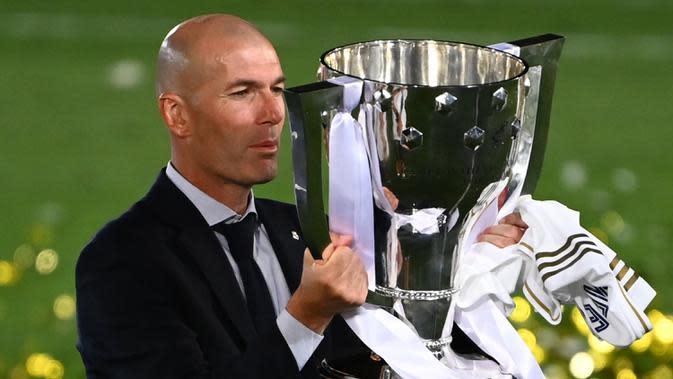 Pelatih Real Madrid, Zinedine Zidane, mengangkat trofi juara La Liga musim 2019/2020 usai timnya mengalahkan Villarreal pada laga lanjutan La liga di Estadio Alfredo Di Stefano, Jumat (17/7/2020) dini hari WIB. (AFP/Gabriel Bouys)