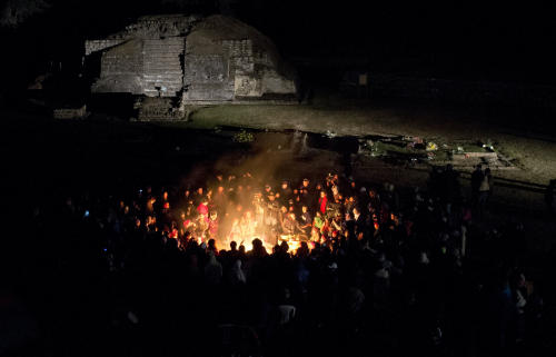 People gather around a sacred fire at the Mayan archeological site of Iximche during a ceremony marking the end of the 13th Oxlajuj B'aktun in Tecpan, Guatemala, early Friday, Dec. 21, 2012. The end of the 13th Oxlajuj B'aktun marks a new period in the Mayan calendar, an event only comparable in recent times with the new millennium in 2000. While the Mayan calendar cycle has prompted a wave of doomsday speculation across the globe, few in the Mayan heartland believe the world will end on Friday. (AP Photo/Moises Castillo)