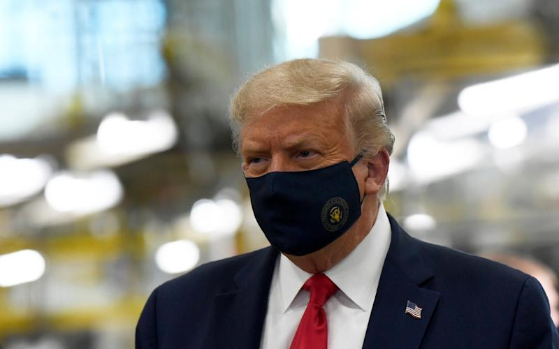 Donald Trump pictured wearing a face mask  - AP