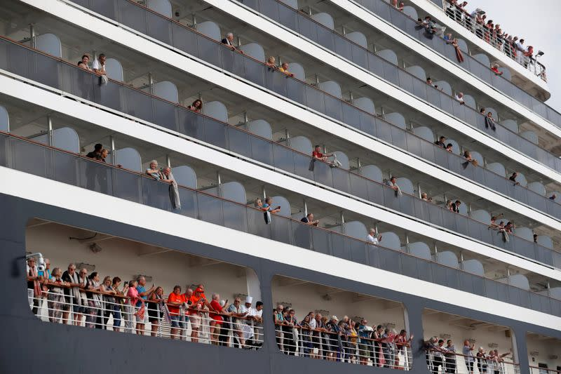 Passengers wave their towels as they are about to leave MS Westerdam, a cruise ship that spent two weeks at sea after being turned away by five countries over fears that someone aboard might have the coronavirus, as it docks in Sihanoukville